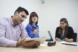 Tre deltagere i et møde diskuterer aktivt
