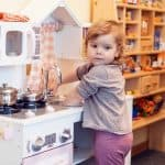Lille pige laver mad på legetøjskøkken