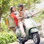 Midaldrende par på scooter med indkøbsposer